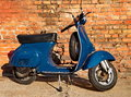 Blue scooter in front of a red brick wall Stock Images