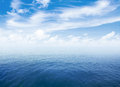 Blue sea or ocean water surface with horizon and sky clouds Royalty Free Stock Images