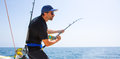 Blue sea offshore fishing boat with fisherman Stock Photo