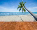 Blue sea, white sand, coconut palm tree and blue sky with wooden bridge walkway in Summer background. Summer beach fresh concept.