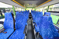 Blue seats for passengers in saloon of empty city bus with grey floor Royalty Free Stock Photos