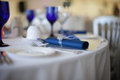 Blue serviette detail on a wedding table formal set with and white linen and elegant matching glassware selective focus with Royalty Free Stock Photo