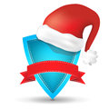 Blue shield with red ribbon and Santa's red hat Royalty Free Stock Photo