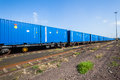 Blue shipping containers train trailers loaded with traveling to harbor depot for export Stock Photography
