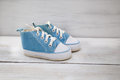 Blue shoes for baby boy on a wooden background Royalty Free Stock Photo