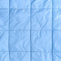 Blue silk quilted fabric as a background Royalty Free Stock Photo