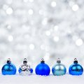 Blue and silver Christmas ornaments in snow with twinkling background Royalty Free Stock Photo
