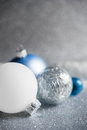 Blue, silver and white xmas ornaments on glitter holiday background. Merry christmas card. Royalty Free Stock Photo