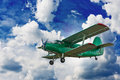 Blue sky with clouds green biplane and Stock Photos