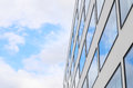 Blue sky and clouds reflected windows of modern building in mirrored new glass facade background with free copy space area for Royalty Free Stock Photos