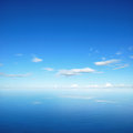 Blue sky and clouds with reflection on sea water Royalty Free Stock Photo