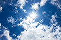 Blue sky with clouds and sun reflection. Royalty Free Stock Photo