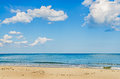 Blue sky with fluffy clouds, over clear sea water,  beach with g Royalty Free Stock Photo