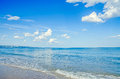 Blue sky with fluffy clouds, over clear sea water,  beach sands, Royalty Free Stock Photo