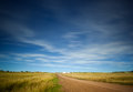 Blue sky light clouds over landscape fields road Royalty Free Stock Photo