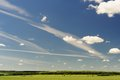 Blue sky with many white clouds and narrow green field copyspace Royalty Free Stock Photo