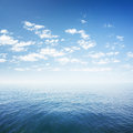 Blue sky over sea or ocean water surface Royalty Free Stock Image
