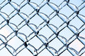 Blue sky refracted by ice on a metal chain link fence close up shot of thick layer of partially covering frozen after an storm the Stock Photos