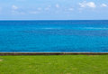 Blue sky sea view with lawn foreground day light Royalty Free Stock Image