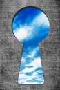 Blue sky seen through the keyhole on a stone background Royalty Free Stock Image