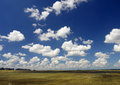 Blue sky and white clouds dark over the field Stock Photography