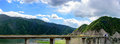 The blue sky, white clouds, green mountains and lake water, the cars driving out of the tunnel are speeding on the viaduct Royalty Free Stock Photo