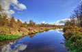 Blue sky and white clouds reflecting on a river to a lake Royalty Free Stock Photo