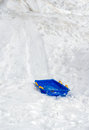 Blue sled on an icy snow hill empty at the bottom of a covered should read just add kids for winter fun Stock Images