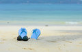Blue slippers and sunglass on the beach white Royalty Free Stock Images