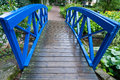 Blue small bridge over river stream creek in garden nature green and landscape Stock Photo