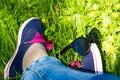 Blue sneakers and jeans on the legs of a woman sitting on the gr Royalty Free Stock Photo