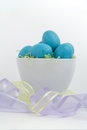 Blue speckled eggs in easter grass with pastel ribbon brightly colored a white bowl sheer ribbons Stock Image