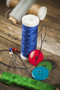 Blue spool of sewing thread single and buttons scattered around Stock Image