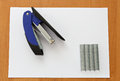Blue stapler and staples with paper Royalty Free Stock Photo