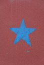 Blue star on the burgundy wall. A concept photograph.
