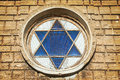 Blue star of david in the window yellow wall at background Royalty Free Stock Photography