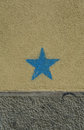 Blue star on the dirty ochre and gray wall. A concept photograph.