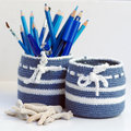 Blue stationery and white nesting bowls in crochet with stack of pencils and Royalty Free Stock Photo