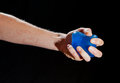 Blue stress ball in a female hand to exercice the muscles of your underarm hold by on black background Royalty Free Stock Images