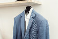 Blue suit jacket with a white shirt on the rack