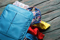 Blue suitcase overfilled with clothes. Royalty Free Stock Photo