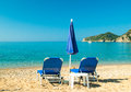 Blue sunbeds and blue umbrella on a the beach in corfu island greece parasols into sun tropical Royalty Free Stock Photography