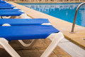 Blue sunbeds surrounding a swimming pool Stock Images