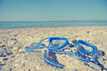 Blue swimming goggles on the beach; faded, retro style Royalty Free Stock Photo