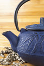 Blue teapot with bamboo shoots japanese cast iron black handle and brewing hand rolled green tea and jasmine petals on wooden Royalty Free Stock Image