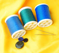 Blue threads set thread and needles with buttons on yellow clothes Royalty Free Stock Photo