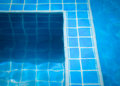 Blue tiles in swimming pool water Stock Photos