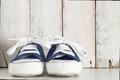 Blue toddler sneakers against a white wooden background empty copy space for editor s text Stock Images