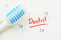 Blue toothbrush on dentist appointment reminder on a calendar.
