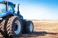 Blue tractor on the background of an empty field Royalty Free Stock Photo